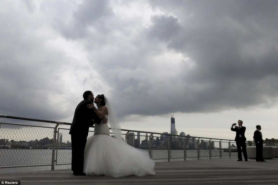 Ominous future: Newlyweds Kyle Legman and Michelle Sheivachman pose for their wedding pictures under storm clouds, across from New York's Lower Manhattan