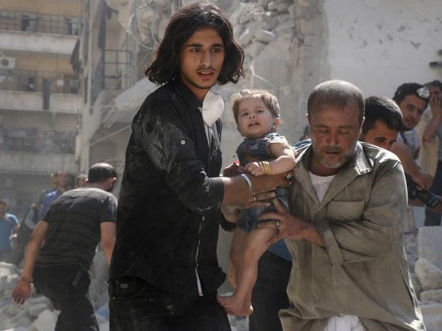 Voluntário e membro da defesa civil da Síria carregam bebê encontrada sob escombros de um edifício destruído depois de um ataque aéreo no norte de Aleppo (Foto:  Thaer Mohammed/AFP)