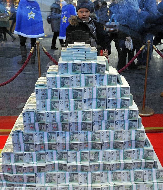 Menino observa o principal prêmio da loteria polonesa em dezembro que foi exposto em formato de pirâmide em um shopping na Polônia. Pesando 210 quilos, a pirâmide consiste em notas de dinheiro que equivalem a 23,378,863 Zlotys (moeda polonesa), ou US$ 7,792,954.