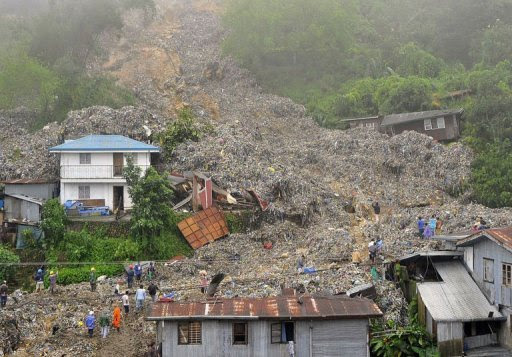 Rubbish swamps houses after heavy rains from Typhoon Nanmadol caused a  retaining wall at a landfill to collapse