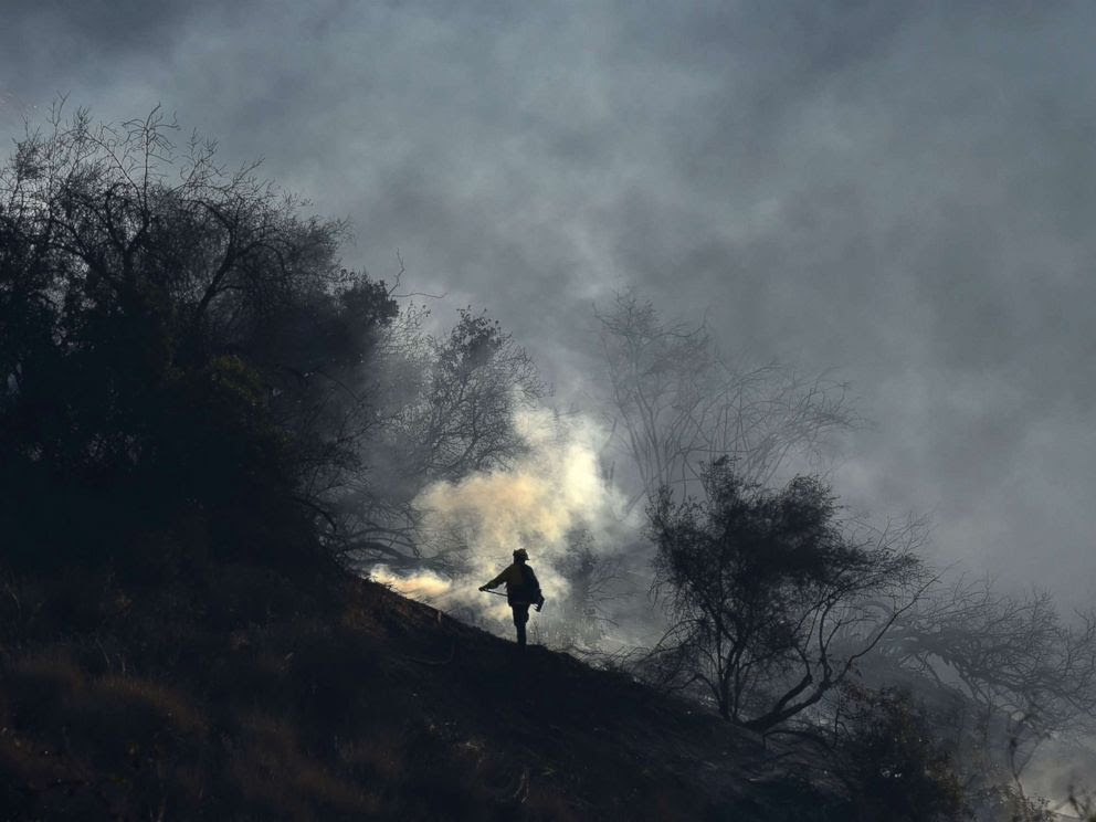 PHOTO: A member of a fire team hand crew monitors embers to prevent fire from jumping to the west side of the 405 freeway, at the Skirball Fire near the Bel Air area of Los Angeles, Dec. 6, 2017.