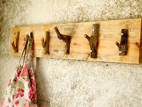 Cabideiro de galhos secos fixos num suporte de madeira
