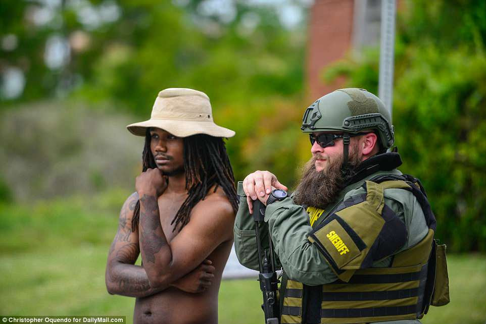 Un ciudadano local sin camisa ve la escena junto a un diputado asignado para mantener a los manifestantes separados de los neonazis