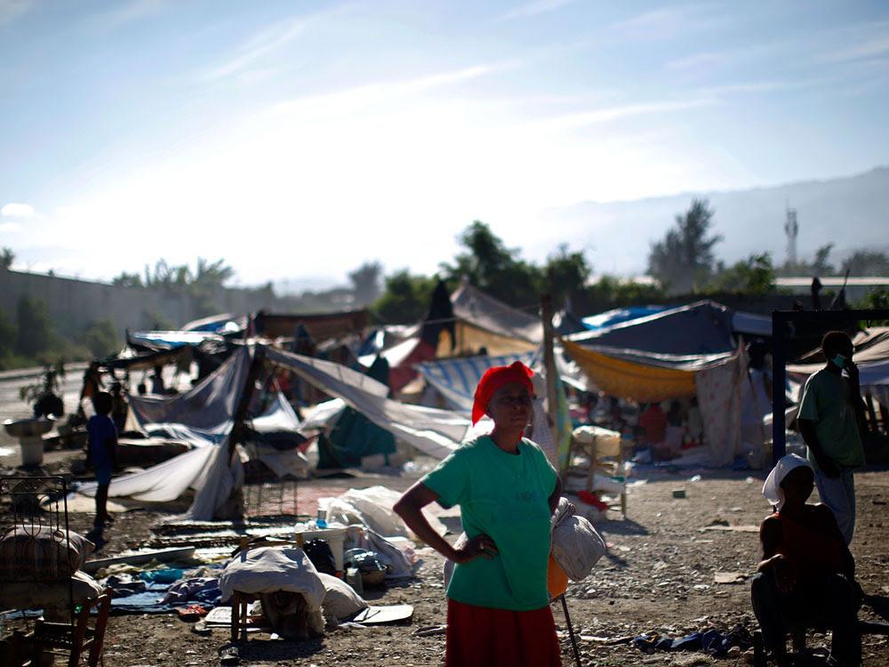 A woman stands near a makeshift refugee camp near downtown Port-au-Prince