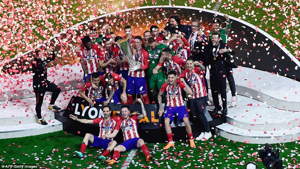 The Atletico Madrid players are showered in confetti as they pose with their Europa League trophy after a 3-0 win on the night