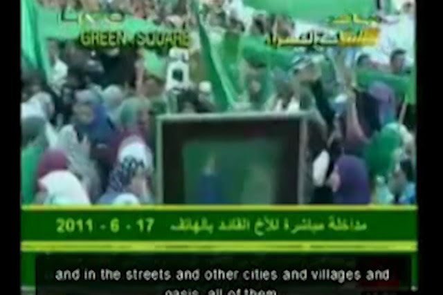Screenshot @ 0:04:57 Speech_Gaddafi_June_17_2011_English_subtitles_during_mass_demonstration_in_Tripoli-Rt3l_dm0zhE