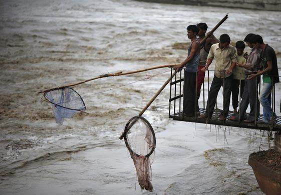 People hold nets to catch floating watermelons in the flooded waters of river Yamuna after heavy monsoon rains in New Delhi, June 18, 2013.  REUTERS-Ahmad Masood