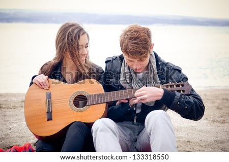 Young girl with acoustic guitar and her boyfriend on the beach