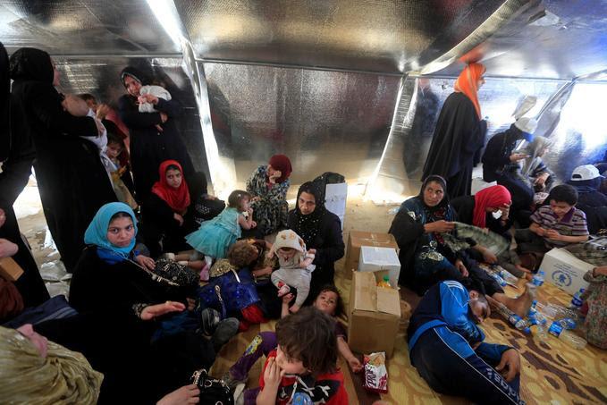 Des familles fuyant l'Etat islamique attendent d'être fouillées à un check point de Mossoul. L'armée irakienne craint la présence de kamikazes parmi eux
