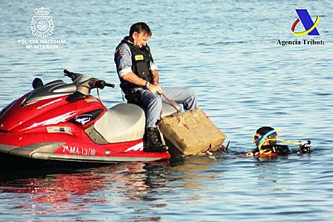 Dos agentes recuperan un fardo de droga enganchado a una moto acuática.