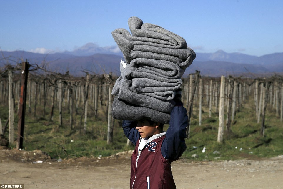 A young boy carries blankets on his head as he finally crosses into Macedonia from Greece on Thursday