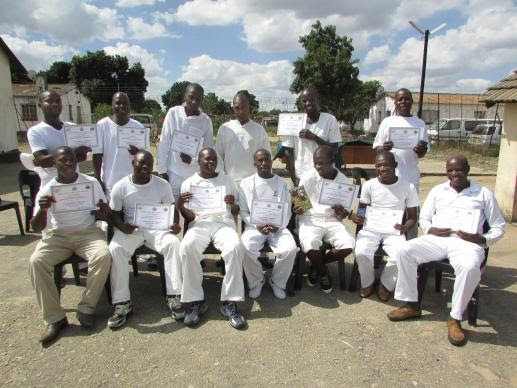 Inmates at Kentucky Prison in Harare, Zimbabwe, pose with their graduation certificates from a yearlong nutritional gardening course. Photo by Kudzai Chingwe.