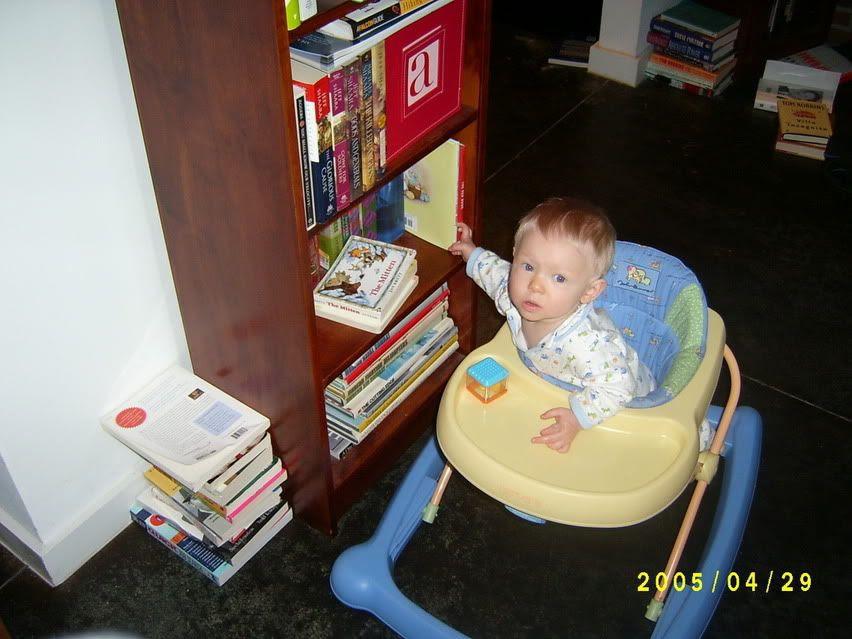 Gabriel reaching for a book on his bookshelf