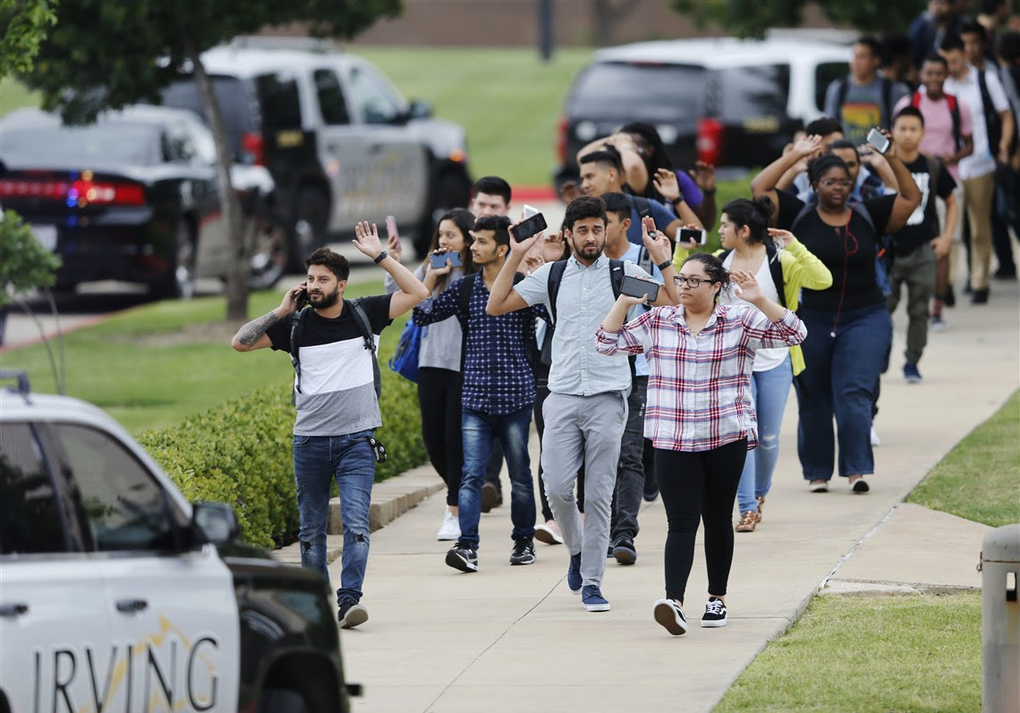 Students and faculty exit a building with their hands up after a fatal shooting at North Lake College in Irving, Texas, on Wednesday. Multiple people died in an apparent murder-suicide at the college, prompting an active-shooter alert that instructed students and employees to barricade themselves into rooms.