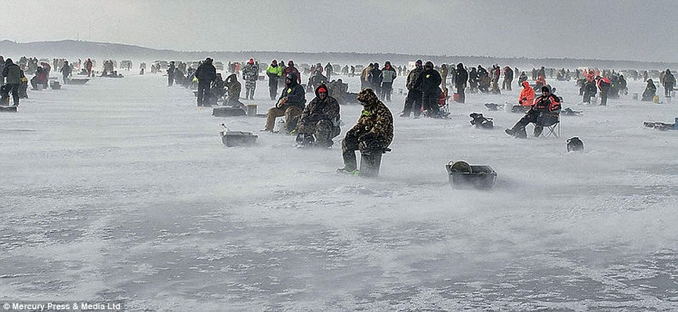 Rows and rows of fishermen wait by their ice holes wrapped in the very thickest of winter gear