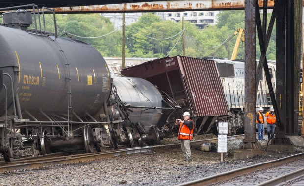BNSF investigators photograph the scene where a locomotive and a handful of cars carrying crude oil went off the track beneath the Magnolia Bridge in Seattle's Interbay neighborhood early this morning.  (Photo by Mike Siegel / The Seattle Times)
