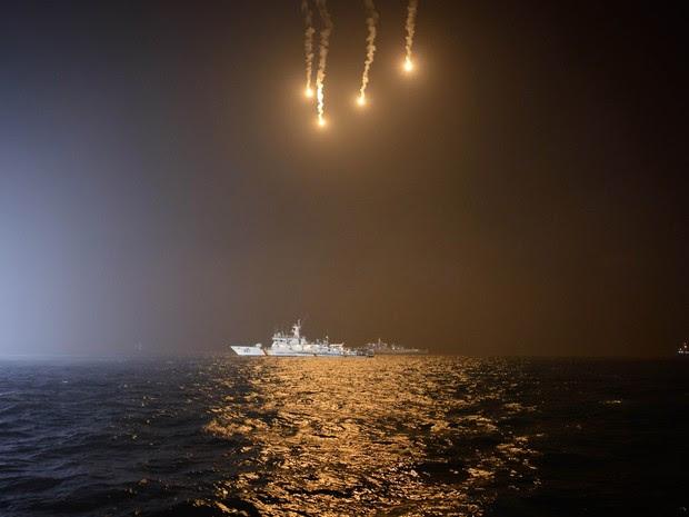 Sinalizadores iluminam o mar enquanto embarcações da guarda costeira sul-coreana buscam desaparecidos no naufrágio de balsa em Jindo  (Foto: Ed Jones/AFP)