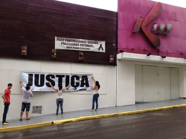 Familiares de vítimas penduram cartazes de protesto na fachada da Kiss (Foto: Bruna Taschetto/RBS TV)