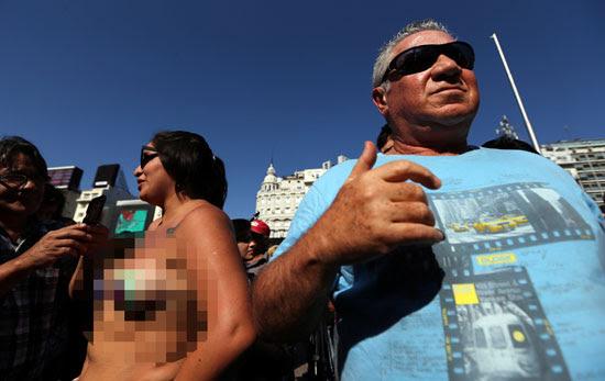 رجل-يقف-بجوار-سيدة-عارية-الصدر-خلال-التظاهرة