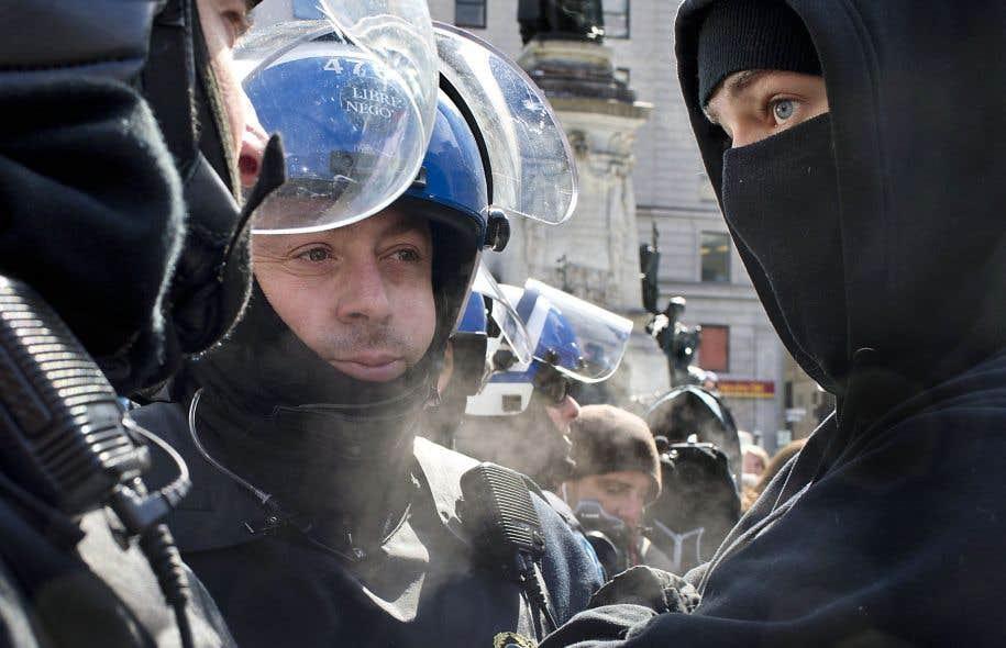Un jeune homme masqué regarde un policier lors d'une manifestation au square Phillips, le 23mars dernier.
