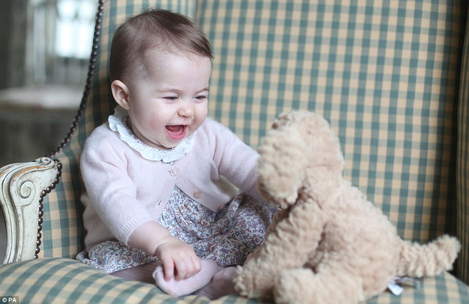 Snapped by her adoring mother, the Duchess of Cambridge, this is little Princess Charlotte at six months old.The princess can be seen sitting unaided in a green checked armchair and in one shot is smiling at a toy puppy