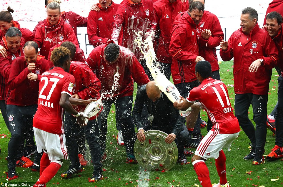 Douglas Costa joined his team-mate as the pair interrupted photographs of Guardiola and his coaching staff to drench them with beer