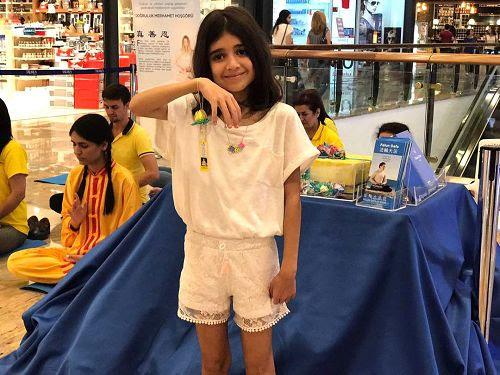'图6:小女孩Melek高兴的展示她得到的真相莲花结'