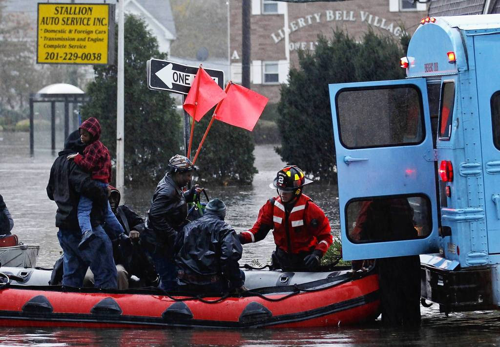 Residents are rescued by emergency personnel from flood waters brought on by Hurricane Sandy in Little Ferry, New Jersey. Millions of people across the eastern United States awoke on Tuesday to scenes of destruction wrought by monster storm Sandy, which knocked out power to huge swathes of the nation's most densely populated region, swamped New York's subway system and submerged streets in Manhattan's financial district.