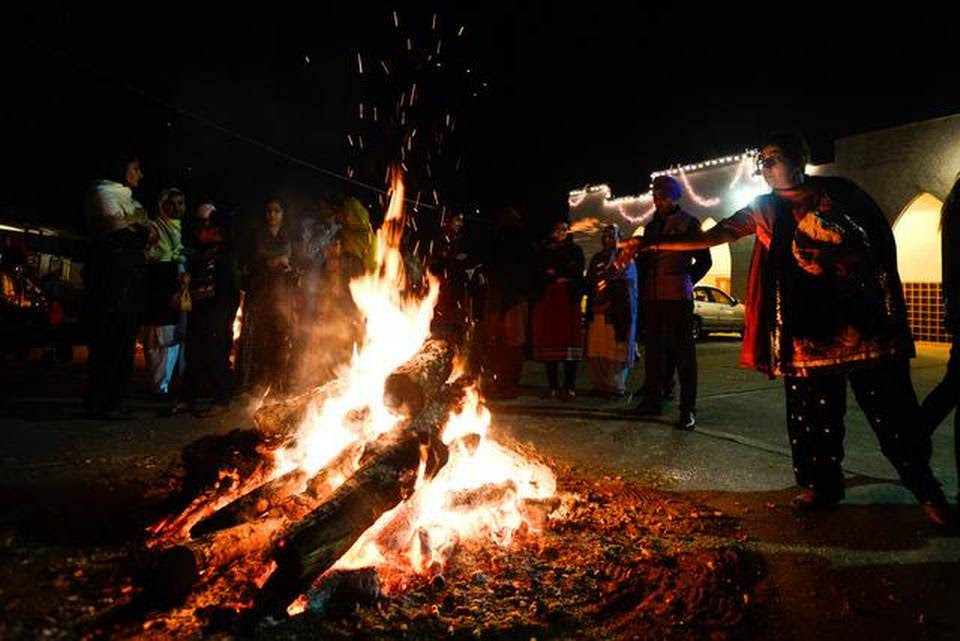 Food is tossed into the fire during Lohri, a Punjabi festival, in Livingston on Tuesday.