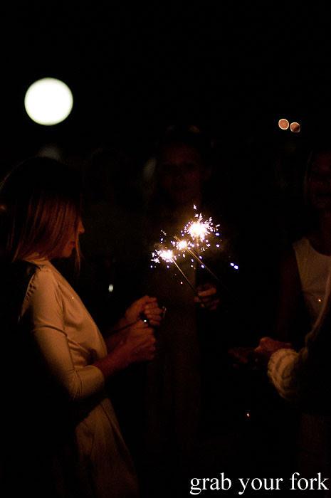 Lighting sparklers at Diner en Blanc Sydney 2013 Bondi Beach