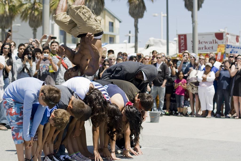 Street performer jumps over the crowd of volunteers...