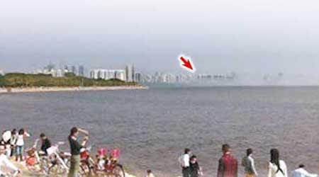 有網民上傳在深圳見到海市蜃樓(箭嘴右方開始),多名市民在岸邊舉機拍攝奇景。(互聯網圖片)