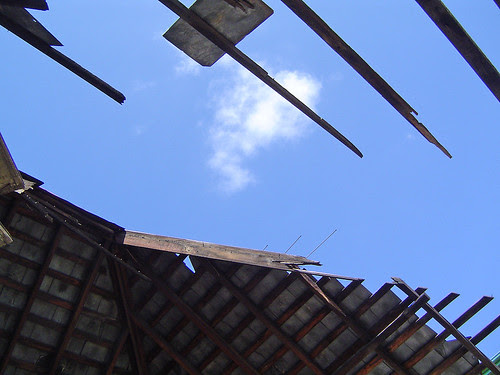 bones and sky - remains of a slate tile roof and blue sky behind