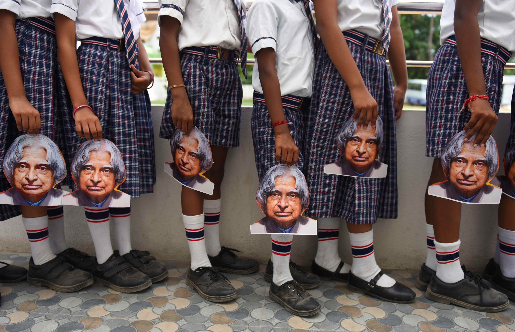 TOPSHOT - Indian schoolchildren hold masks bearing the image of former Indian president A.P.J Kalam ahead of the first anniversary of his death during a remembrance event at a school in Chennai