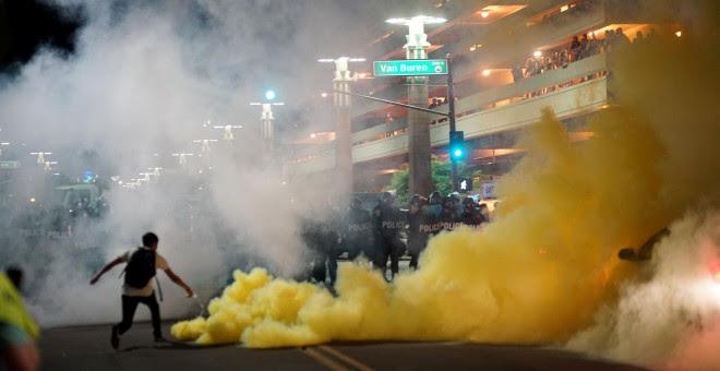 Los cuerpos de policía lanzando gas para dispersar a los manifestantes que se agolparon en el exterior del centro de convenciones en el último mitin de Donald Trump en Phoenix, Arizona. REUTERS/Sandy Huffaker