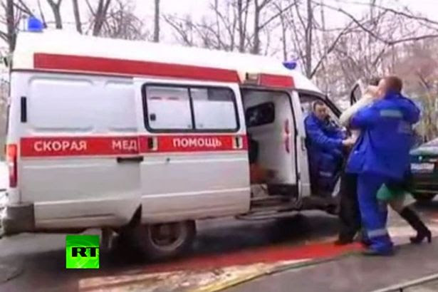 The mother of the decapitated child is taken to a waiting ambulance