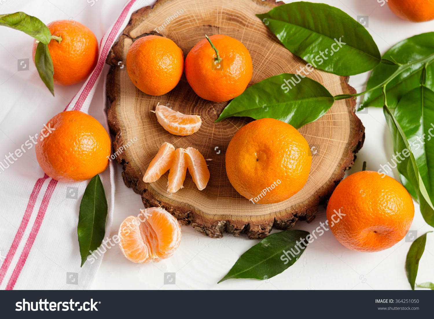 http://www.shutterstock.com/pic-364251050/stock-photo-fresh-mandarins-with-green-leaves-on-white-wooden-background-rustic-composition-with-shallow-focus.html