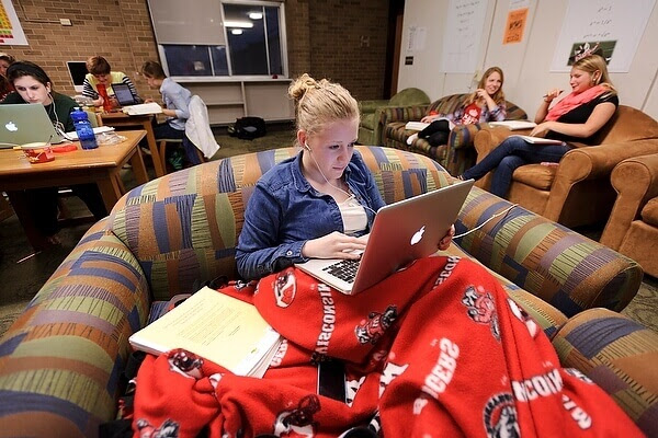 Photo: Student with laptop wearing earbuds