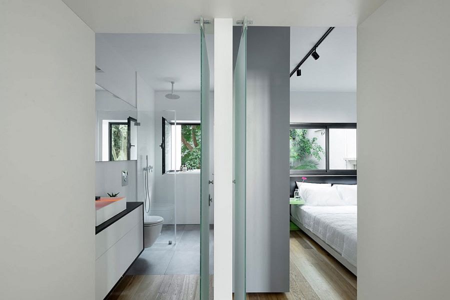 Glass walls separate the master bedroom from the bathroom
