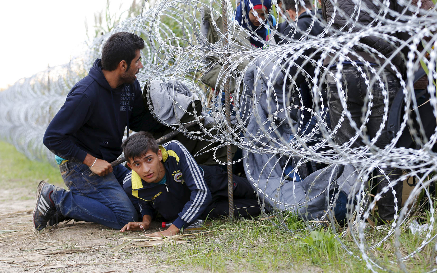 Syrian migrants cross under a fence at Hungarian-Serbian border near Roszke
