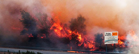 Flames ravage the forest near the highway in La Jonquera, near the border with France, Spain. The regional officials said wildfires have burned almost 7,000 hectares (17.297 acres) of forest. Sign at right is an environmental road traffic poster. (AP Photo/Josep Rivas)