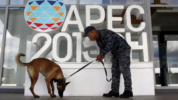 A soldier uses a canine to check the surroundings of the International Media Center during the security preparation for the Apec summit in Manila on 12 November, 2015