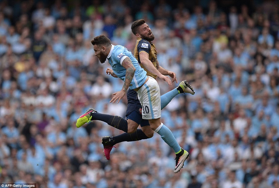 Arsenal's French striker Giroud jumps for a header with Manchester City's Argentinian defender Nicolas Otamendi