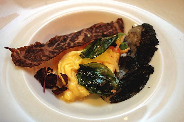 Hokkaido scallops cured with gunpowder, white pepper and caviar scrambled eggs, dehydrated wagyu and fried basil