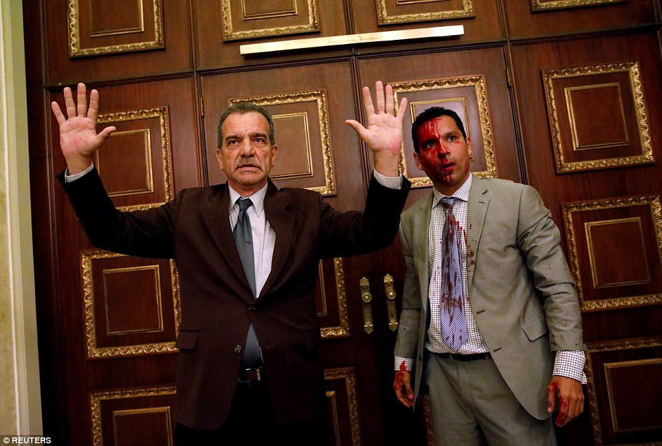 Opposition lawmaker Luis Stefanelli stands with opposition legal colleague Leonardo Regnault after a group of government supporters burst into Venezuela's opposition-controlled National Assembly during a session in the country's capital, Caracas, on July 5