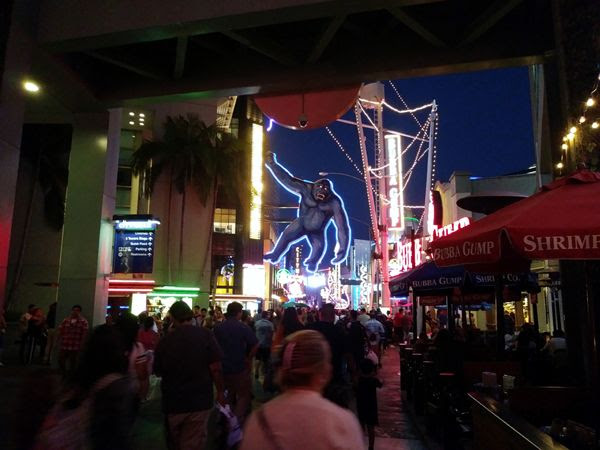 A crowd of people walk towards a KING KONG neon sign at Universal CityWalk in North Hollywood...on August 26, 2018.