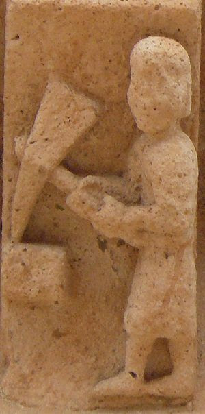 A medieval stonemason at work as shown in a co...