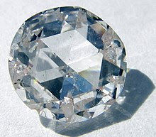 A round, clear gemstone with many facets, the main face being hexagonal, surrounded by many smaller facets.