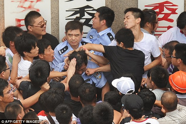 Protesters beat a policeman having come out to protest against plans for an industrial waste pipeline