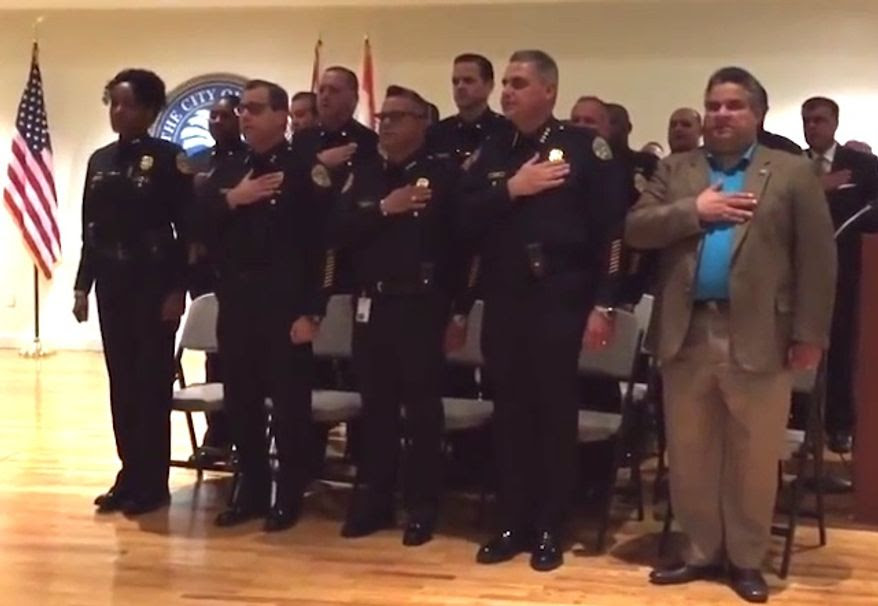Miami's top police union representative is facing backlash from the city's oldest black police organization after he called for a reprimand against Assistant Chief of Police Anita Najiy (pictured on the far left) and questioned her Muslim faith when she failed to salute the American flag. (YouTube/Miami Herald)